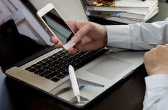 Рука бизнесмена используя телефон на портативном компьютере Стоковая Фотография RF