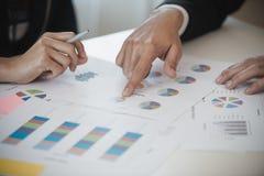 Рука бизнесмена и бизнес-леди работая на диаграммах данных, d Стоковые Фотографии RF