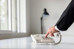 Рука бизнесмена набирая номер телефона стоковая фотография
