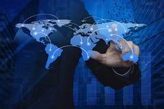 Рука бизнесмена нажимая глобальную карту ov соединения мирового бизнеса