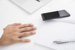 Рука бизнесмена на столе сотовым телефоном, ручкой и книгой Стоковые Фотографии RF