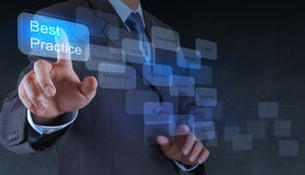 Рука бизнесмена показывает слово передовой практики на виртуальном экране Стоковые Фотографии RF