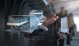 Рука бизнесмена представляет модель дома на современном компьютере Стоковые Фото