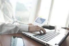 Рука бизнесмена работая на портативном компьютере Стоковое Изображение
