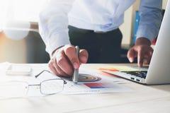 Рука бизнесмена работая с компьтер-книжкой на деревянном столе в офисе смогите быть использовано на объявлении Стоковое фото RF