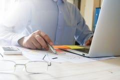 Рука бизнесмена работая с компьтер-книжкой на деревянном столе в офисе смогите быть использовано на объявлении Стоковое Изображение