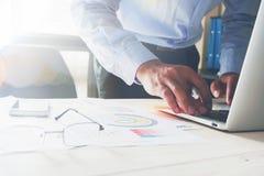 Рука бизнесмена работая с компьтер-книжкой на деревянном столе в офисе смогите быть использовано на объявлении Стоковое Фото