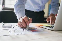 Рука бизнесмена работая с компьтер-книжкой на деревянном столе в офисе смогите быть использовано на объявлении Стоковое Изображение RF