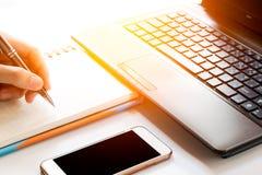 Рука бизнесмена работая с новым современным компьютером и писать на диаграмме стратегии блокнота как свет утра концепции Стоковые Изображения