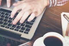 Рука бизнесмена работая с телефоном и компьтер-книжкой на деревянном столе в офисе смогите быть использовано на объявлении Стоковые Фото