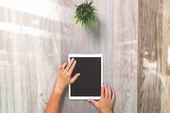 Рука бизнесмена работая с цифровым планшетом На древесине Стоковое Изображение