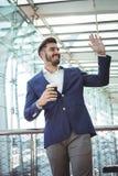 Рука бизнесмена развевая пока имеющ кофе на железнодорожном вокзале Стоковое Изображение