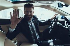 Рука бизнесмена развевая пока управляющ автомобилем стоковое изображение
