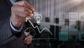 Рука бизнесмена рисует лампочку с новым интерфейсом компьютера стоковые изображения rf