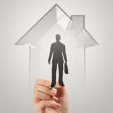 Рука бизнесмена рисуя дом 3d с человеческим значком Стоковая Фотография