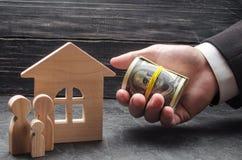 Рука бизнесмена удлиняет деньги к деревянному дому Семья стоит около дома Концепция покупать стоковое фото rf