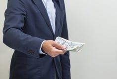 Рука бизнесмена хватая USD Стоковое фото RF