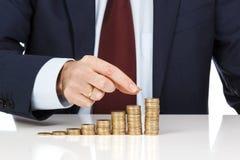 Рука бизнесмена штабелируя одно евро чеканит в увеличивая столбцы Стоковые Изображения RF