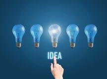 Рука бизнесмена щелкает дальше кнопку идея и осветила лампу стоковое изображение