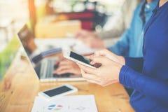 рука бизнес-леди работая на умных телефоне и портативном компьютере a Стоковые Фото