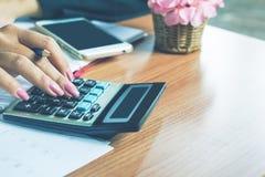 рука бизнес-леди высчитывая ее ежемесячные расходы во время налога приправляет Стоковое фото RF