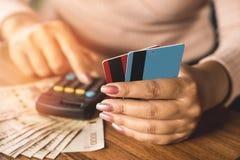 Рука бизнес-леди держа кредитную карточку подсчитывая ее дорогой с калькулятором и деньгами на деревянном столе Стоковые Изображения RF