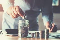 рука бизнес-леди держа монетки кладя в стекло концепция sav стоковое изображение rf