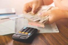 Рука бизнес-леди подсчитывая бумажные деньги денег с книгой и калькулятором сберегательного счета на таблице Стоковые Изображения RF