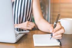 Рука бизнес-леди работая на компьютере и писать на notep Стоковые Фото