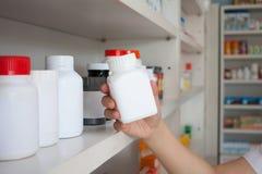 Рука бутылки медицины владением аптекаря женщины Стоковая Фотография RF