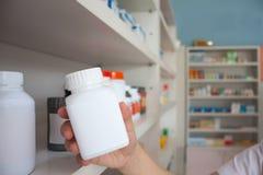 Рука бутылки медицины владением аптекаря женщины Стоковые Изображения