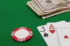 Рука блэкджека с примечаниями доллара и обломок на зеленом цвете Стоковые Изображения