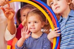 Рука волны маленькой девочки смотря однако обруч Стоковая Фотография