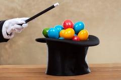 Рука волшебника при волшебная палочка принося пасхальные яйца в трудном Стоковое фото RF