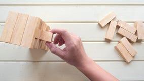 Рука - выберите вверх деревянный блок для того чтобы сделать структуру на деревянной предпосылке, p Стоковое Фото