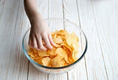Рука выбирает вверх картофельные стружки стеклянных шаров, вредной еды Стоковое Изображение RF
