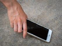 Рука выбирая сломанный умный телефон земли Стоковое Фото