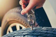 Рука вытягивая для извлекать ноготь в автошине, отладке спущенной шины и ремонтирует автошину протекает от тэкса стоковые изображения rf