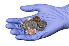 Рука в голубой перчатке латекса с кучей американских монеток Стоковая Фотография RF