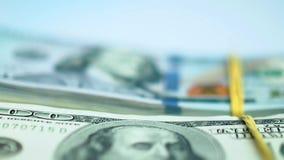 Рука в голубой перчатке кладет пачки пачек доллара США на белую поверхность closeup видеоматериал