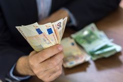 Рука в костюме держа 50 и 100 примечаний счета евро Стоковое Изображение