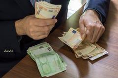 Рука в костюме держа 50 и 100 примечаний счета евро Стоковое Фото