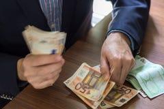 Рука в костюме держа 50 примечаний счета евро Стоковая Фотография