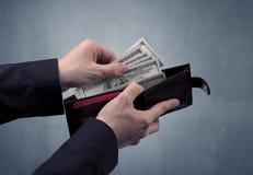 Рука в костюме принимает вне доллар от бумажника Стоковые Фотографии RF