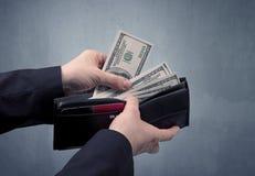 Рука в костюме принимает вне доллар от бумажника Стоковая Фотография