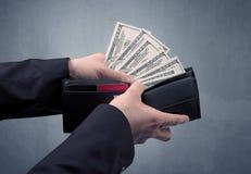 Рука в костюме принимает вне доллар от бумажника Стоковые Фото