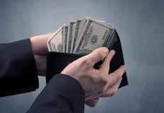 Рука в костюме принимает вне доллар от бумажника Стоковая Фотография RF