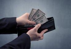 Рука в костюме принимает вне доллар от бумажника Стоковое Фото