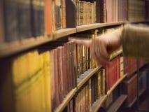 Рука в магазине с античными книгами Стоковое Изображение