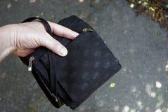 Рука в открытой малой черной сумке на улице стоковые фото
